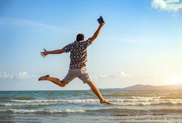 Szczęśliwy mężczyzna wolności skoku oceanu morza głąbika tło