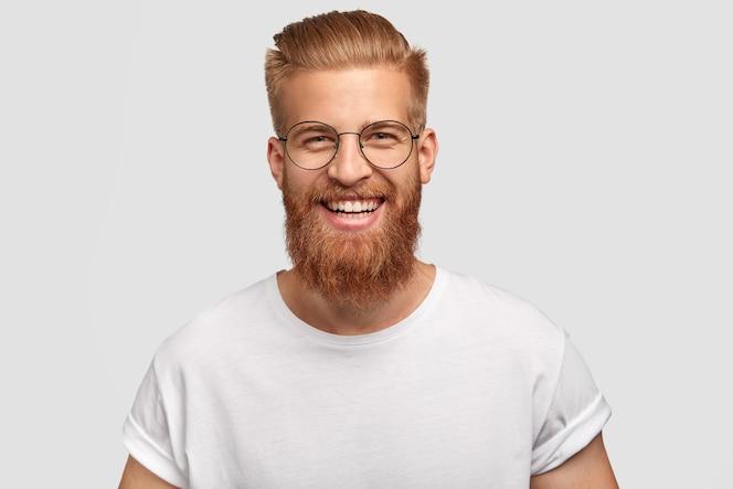 Szczęśliwy mężczyzna z długą, gęstą rudą brodą, ma przyjazny uśmiech
