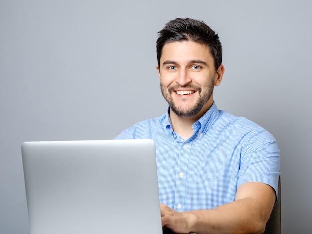 Szczęśliwy mężczyzna z laptopem odizolowywającym na szarość
