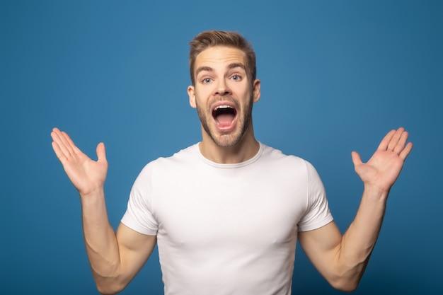 Szczęśliwy mężczyzna z otwartym usta i otwartymi rękami odizolowywającymi na błękicie