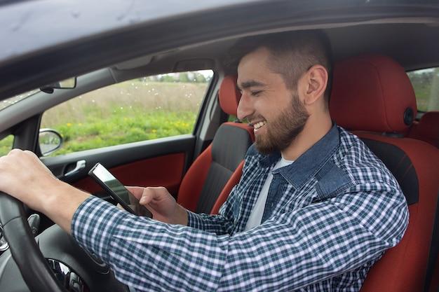 Szczęśliwy mężczyzna zagląda do telefonu w samochodzie