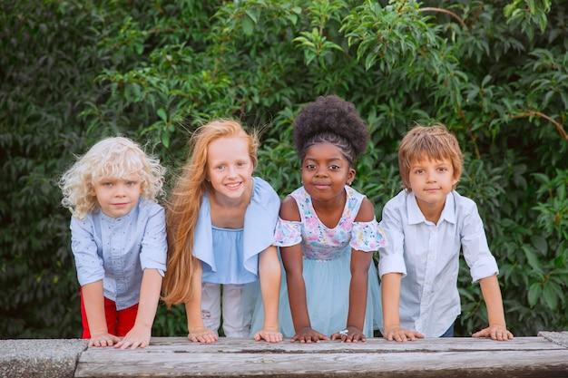 Szczęśliwy. międzyrasowa grupa dzieci, dziewcząt i chłopców grających razem w parku w letni dzień. przyjaźń nie ma rasy.