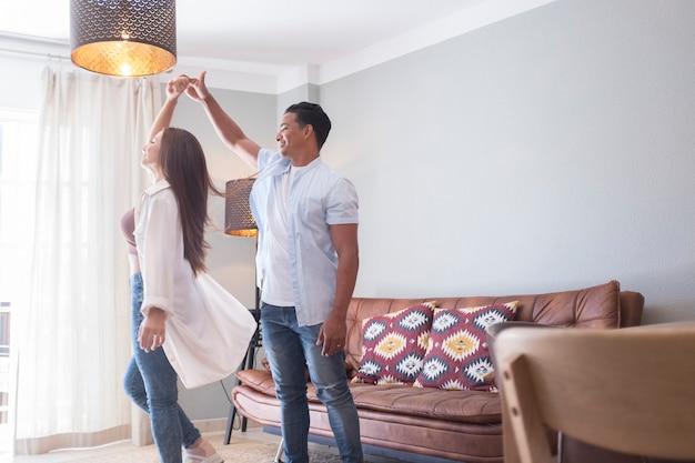Szczęśliwy mieszanej rasy etnicznej mąż i żona czują się podekscytowani, tańcząc, kołysząc się, stojąc w domu