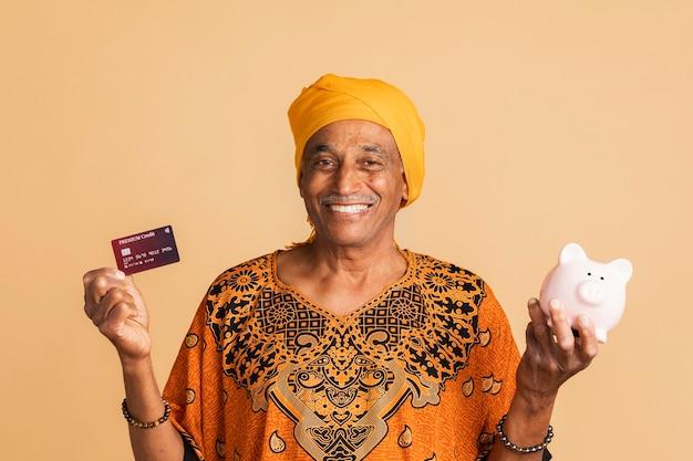 Szczęśliwy mieszany indianin z kartą kredytową i skarbonką