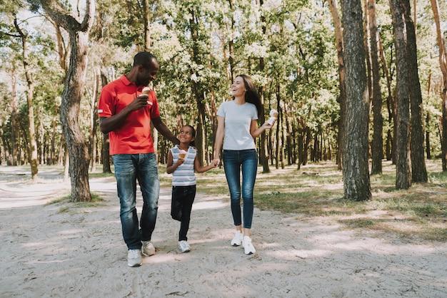 Szczęśliwy mieszany rodzinny łasowanie lody w lesie.