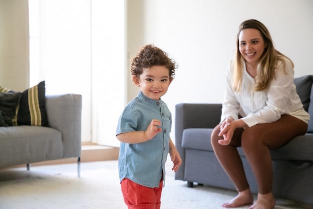 Szczęśliwy mieszany ścigany kręcone mały chłopiec stojący w salonie. blond matka długowłosy siedzi na kanapie i uśmiecha się. selektywna ostrość. pojęcie czasu dla rodziny, macierzyństwa i weekendu