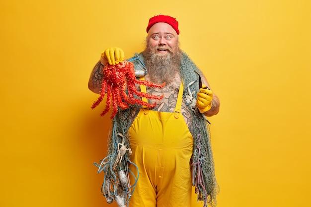 Szczęśliwy miło zaskoczony bosman z brodą chwali się, jaką wielką ośmiornicą złapał, trzyma fajkę, ma morską przygodę, nosi żółty kombinezon, nosi sprzęt wędkarski, pozuje w środku, ma duży, gruby brzuch