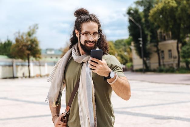 Szczęśliwy miły człowiek, patrząc na ekran smartfona, stojąc na ulicy