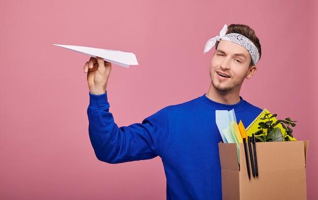Szczęśliwy miły facet retro z pudełkiem z roślinami, długopisami i papierowymi samolotami w ręku strzelał