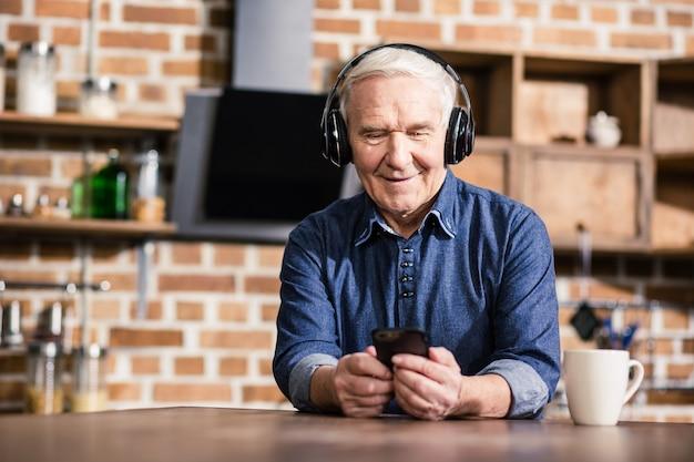 Szczęśliwy miły starszy mężczyzna siedzi w domu podczas słuchania muzyki