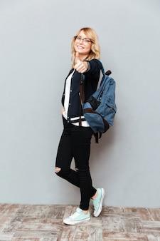 Szczęśliwy młoda dama uczeń jest ubranym szkła z plecakiem
