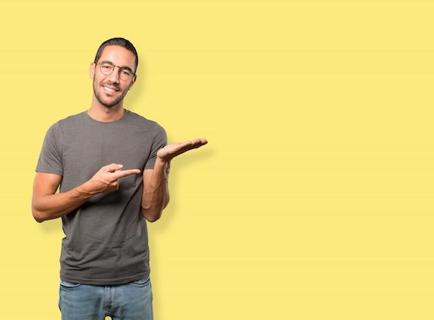 Szczęśliwy młodego człowieka mienie coś z jego ręką