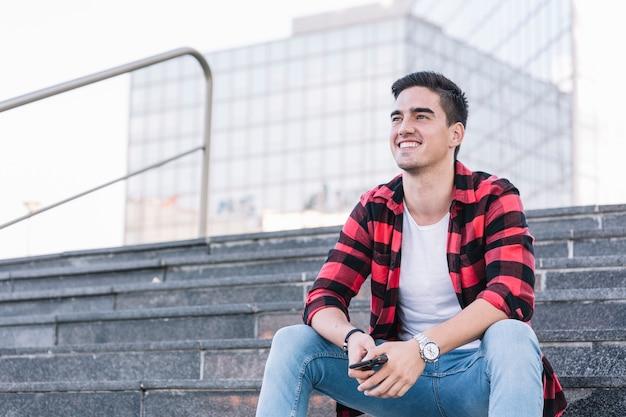 Szczęśliwy młodego człowieka obsiadanie na schody