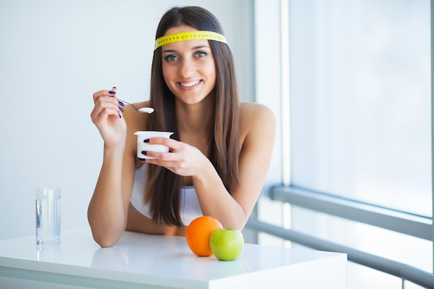 Szczęśliwy młodej kobiety łasowania jogurt w kuchni