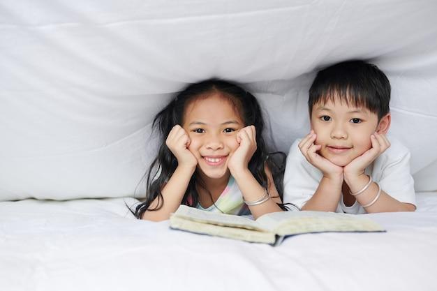 Szczęśliwy młodszy brat i siostra odpoczywają pod kocem z otwartą książką i patrzą w kamerę