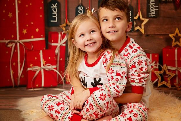 Szczęśliwy młodszy brat i siostra w piżamie bożego narodzenia, czekając na prezenty w wigilię bożego narodzenia
