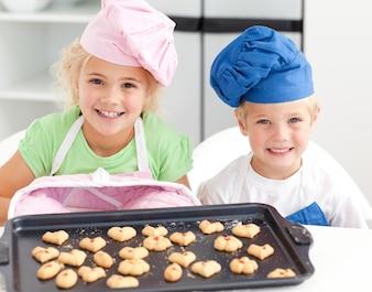 Szczęśliwy młodszy brat i siostra z ich ciastkami przygotowywającymi jeść