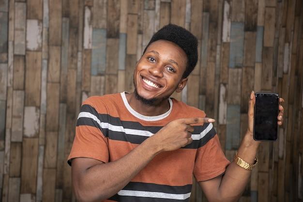 Szczęśliwy młody afrykanin trzymający telefon komórkowy
