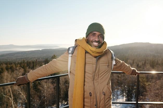 Szczęśliwy młody afrykanin w odzieży zimowej stojący przed kamerą na tle jasnego nieba nad górami i mieszanym lasem w mroźny zimowy dzień