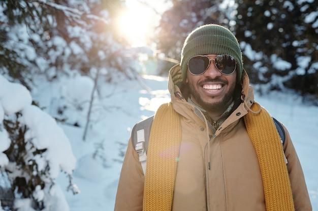 Szczęśliwy młody afrykanin w okularach przeciwsłonecznych i ciepłej odzieży zimowej stojący przed kamerą przed firtrees w śniegu podczas chłodu w zimowy weekend