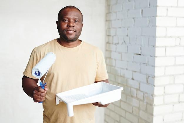 Szczęśliwy młody afrykanin z wałkiem do malowania i białym plastikowym pojemnikiem z farbą stojącą przy dwóch ścianach w swoim nowym mieszkaniu lub domu
