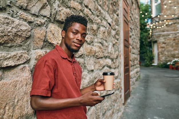 Szczęśliwy młody afrykański człowiek w casualwear, przewijanie w smartfonie i picie