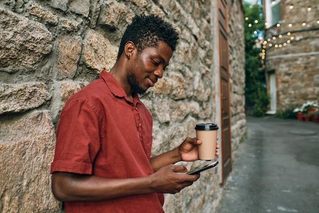 Szczęśliwy młody afrykański człowiek z piciem sms-em w smartfonie