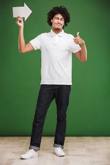 Szczęśliwy młody afrykański kręcone mężczyzna trzyma strzałkę zrobić kciuki gest mrugając.