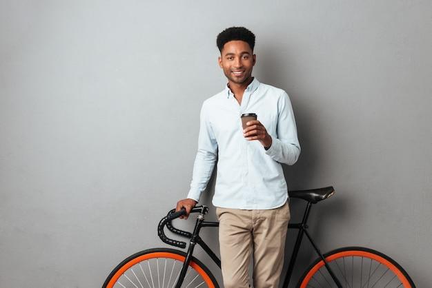 Szczęśliwy młody afrykański mężczyzna pije kawę.