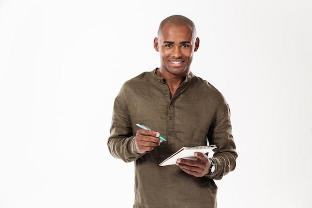Szczęśliwy młody afrykański mężczyzna pisze notatek patrzeć