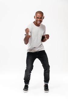 Szczęśliwy młody afrykański mężczyzna robi zwycięzcy gestowi.