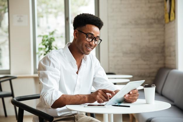Szczęśliwy młody afrykański mężczyzna siedzi coworking