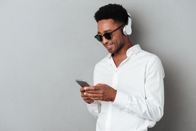 Szczęśliwy młody afrykański mężczyzna słucha muzykę w okularach przeciwsłonecznych