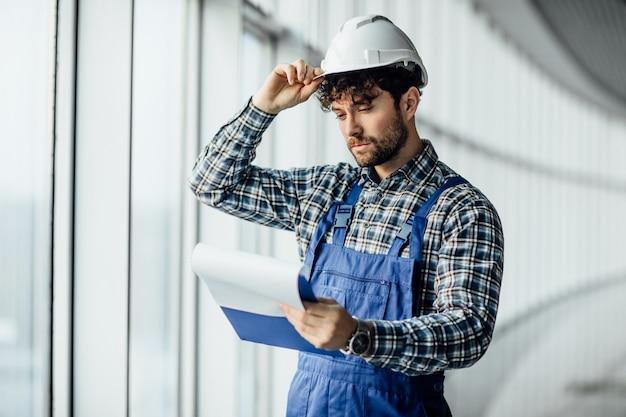 Szczęśliwy młody architekt w kasku trzymającym folder