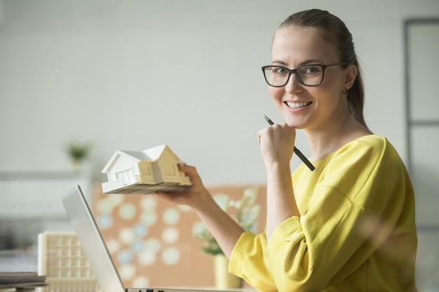 Szczęśliwy młody architekt w okularach i żółtym swetrze trzymając model domu podczas wykonywania kopii na drukarce 3d