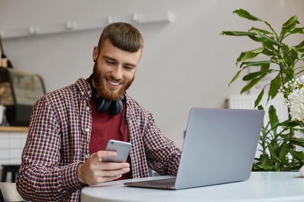 Szczęśliwy młody atrakcyjny brodaty imbir mężczyzna pracuje na laptopie siedząc w kawiarni, ubrany w podstawowe ubrania, szeroko uśmiechnięty i patrząc na swojego smartfona.