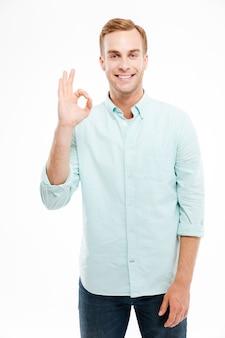 Szczęśliwy młody atrakcyjny mężczyzna pokazując znak ok palcami na białej ścianie