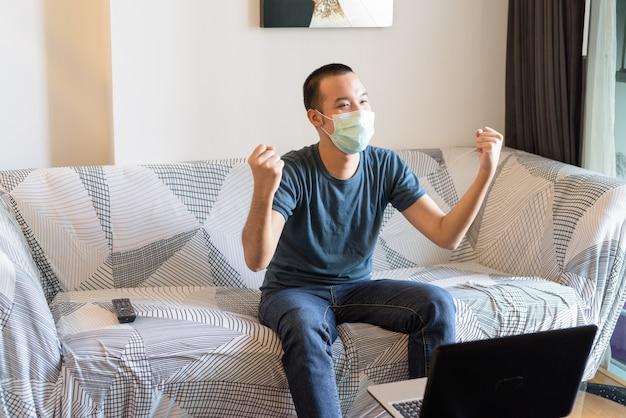 Szczęśliwy młody azjata z maską ogląda telewizję i otrzymuje dobre wieści w domu w ramach kwarantanny