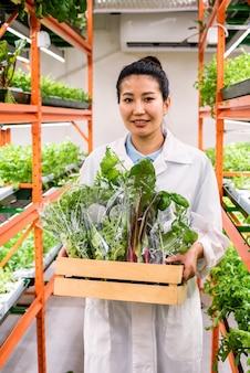 Szczęśliwy młody azjatycki agronom przewożący zapakowaną świeżą żywność ekologiczną w drewnianym pudełku podczas poruszania się wzdłuż przejścia