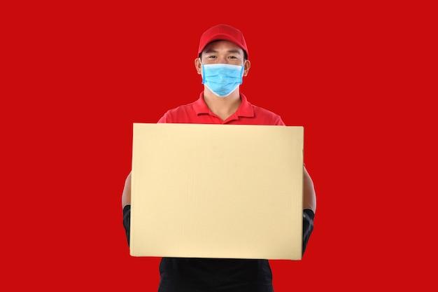 Szczęśliwy młody azjatycki człowiek dostawy w czerwonym mundurze, medycznej masce na twarz, rękawiczkach ochronnych nosi karton w rękach na czerwonym tle. dostawca dostarcza paczkę. podczas epidemii covid-19