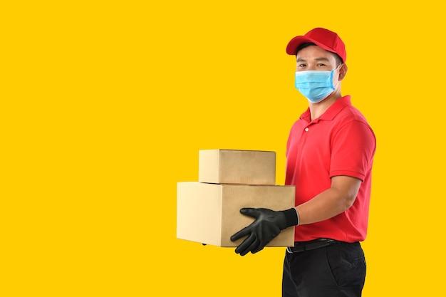 Szczęśliwy młody azjatycki człowiek dostawy w czerwonym mundurze, medycznej masce na twarz, rękawiczkach ochronnych, nosi karton w rękach na żółtej ścianie. dostawca dostarcza paczkę. podczas epidemii covid-19