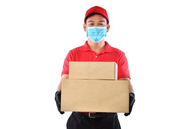 Szczęśliwy młody azjatycki człowiek dostawy w czerwonym mundurze, medycznej masce na twarz, rękawiczkach ochronnych, nosi karton