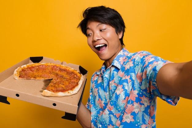 Szczęśliwy młody azjatycki człowiek stojący na białym tle nad żółtą przestrzenią jeść pizzę wziąć selfie przez aparat.
