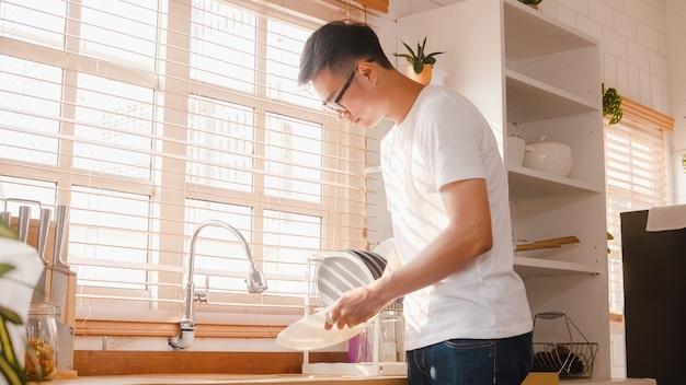 Szczęśliwy młody azjatycki facet zmywa naczynia podczas czyszczenia w kuchni w domu