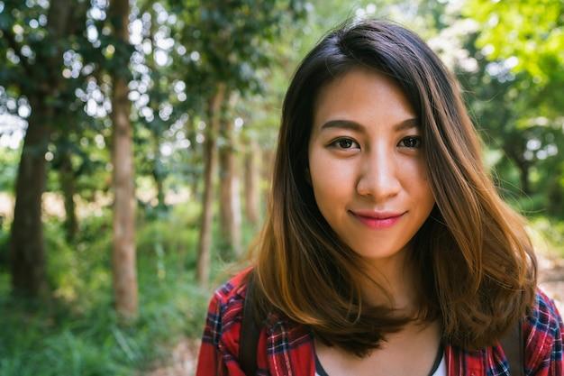 Szczęśliwy młody azjatycki kobieta podróżnik z plecaka odprowadzeniem w lesie.