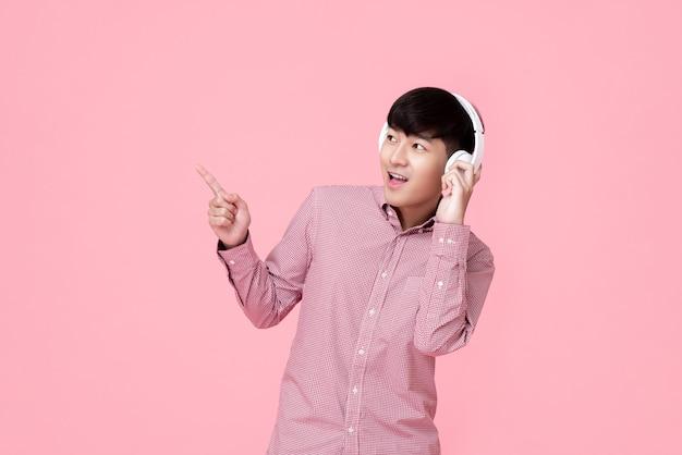 Szczęśliwy młody azjatycki mężczyzna jest ubranym bezprzewodowych słuchawki słucha muzyka
