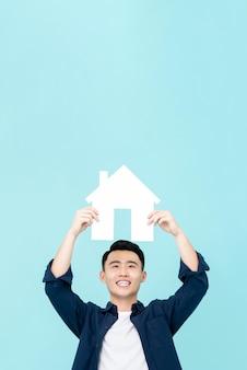 Szczęśliwy młody azjatycki mężczyzna mienia domu znak z kopii przestrzeni koszt stały odizolowywającym na bławej ścianie dla nieruchomości pojęć