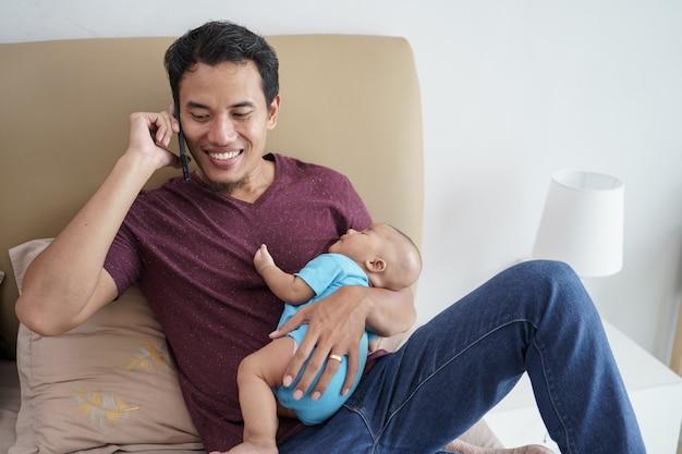 Szczęśliwy młody azjatycki ojciec trzyma jego noworodka słodkie urocze dziecko śpi na ramionach podczas korzystania z telefonu komórkowego na łóżku