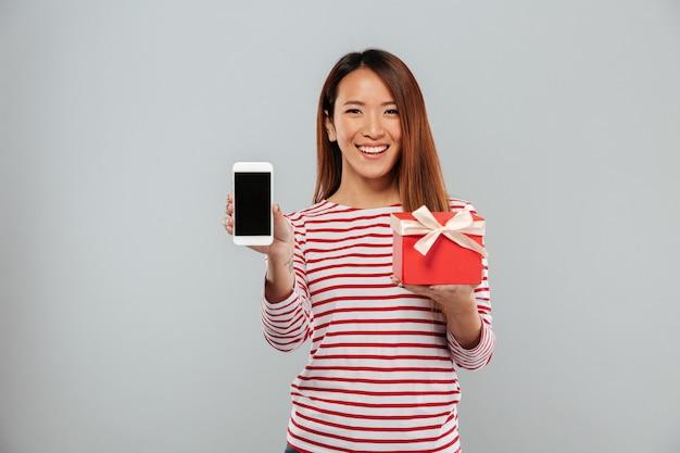 Szczęśliwy młody azjatykci kobieta seansu pokaz telefonu mienia prezent.