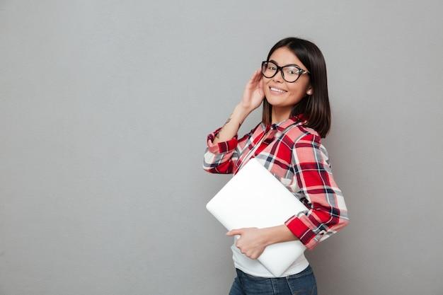 Szczęśliwy młody azjatykci kobiety mienia laptop